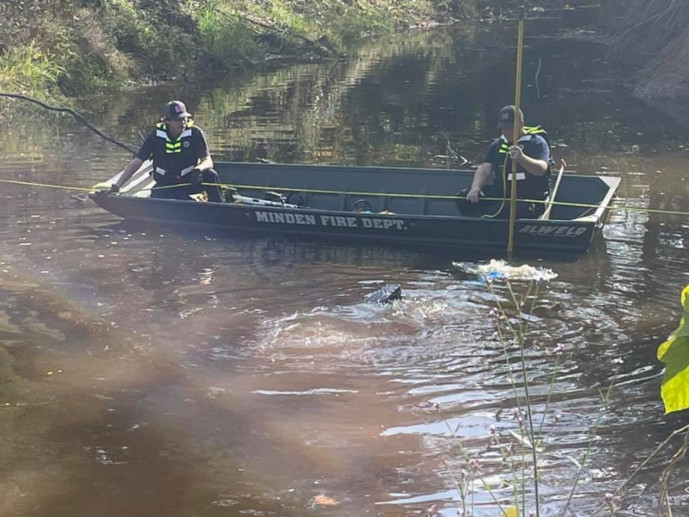Members of the Minden Fire Department dive team search Mile Creek for a murder weapon.
