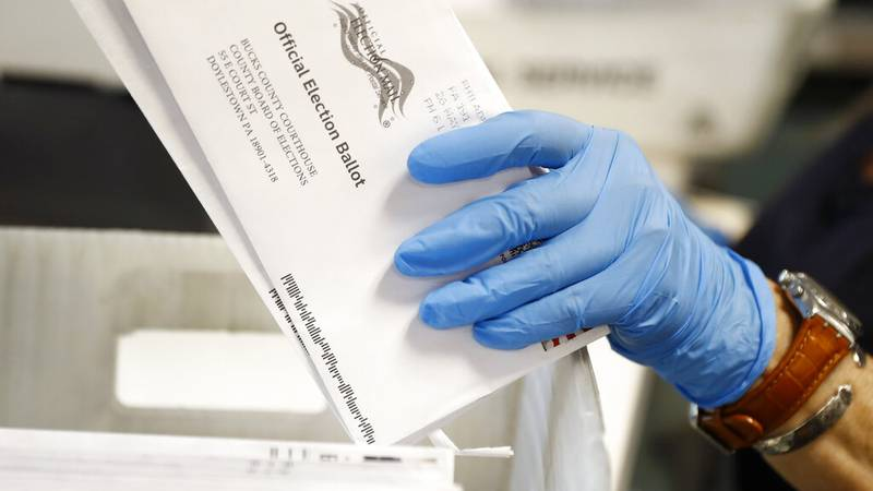 In this May 27, 2020 file photo, a worker processes mail-in ballots at the Bucks County Board...
