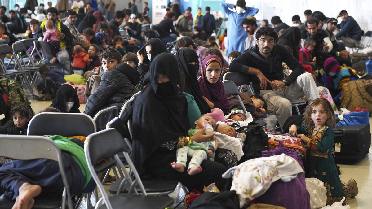 Afghan refugees are seated as they are being processed inside Hangar 5 at Ramstein Air Base in...