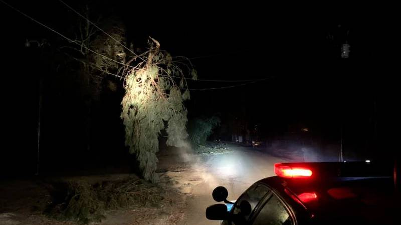 A Livingston Parish sheriff's deputy shines a spotlight from their patrol vehicle on a frozen...