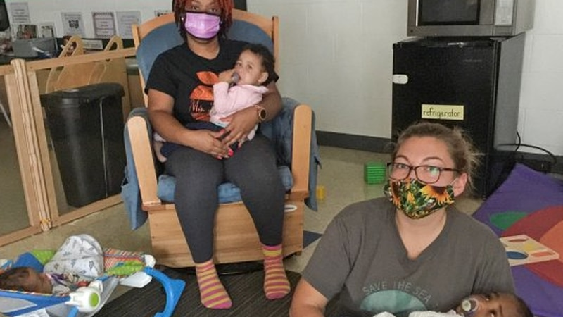 Teachers in masks care for children in the infant room at a daycare run by The Children's...