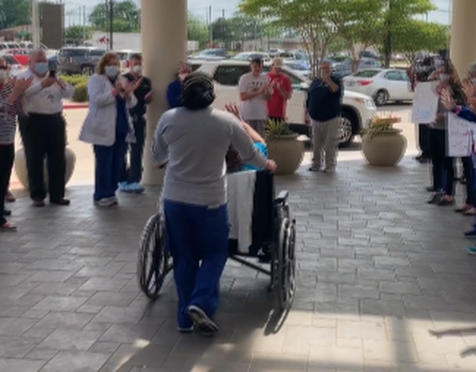 Leigh White is wheeled out to her car after her release from the hospital.