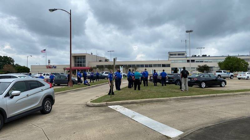 Staff stand outside the Shreveport Regional Airport following evacuation orders from the...