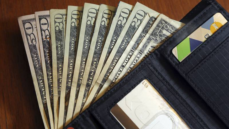 In this June 15, 2018 photo, cash is fanned out from a wallet in North Andover, Mass. (AP...