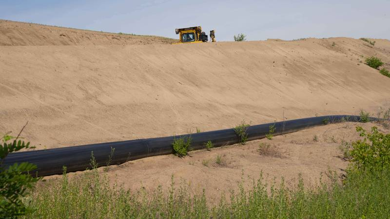 Heavy equipment moves sand dredged from the Mississippi River in Brownsville, Minnesota
