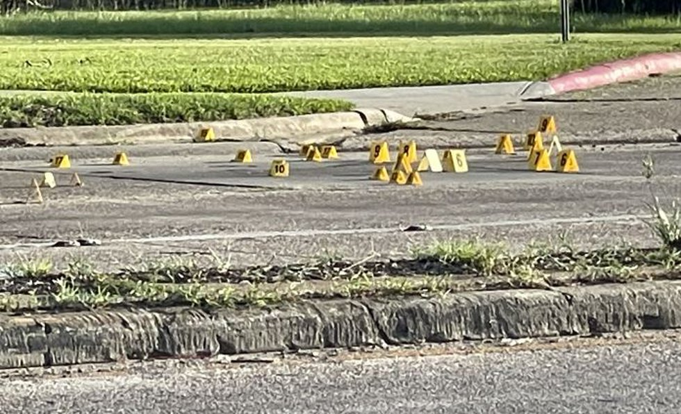 More than two dozen crime scene evidence markers could be seen in the street in front of...