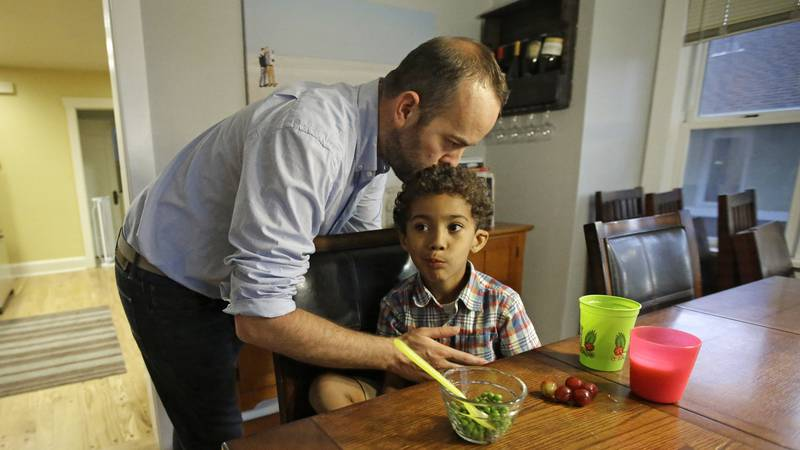 Weston Clark, kisses his son Xander, 4, while he eats at their home in Salt Lake City on...