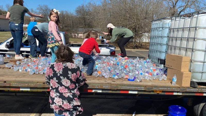 Youths on a flatbed trailer toss bottles of water into the back of a pickup Tuesday in...