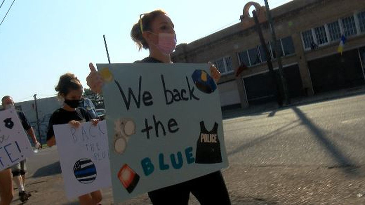 Demonstrators hold signs, wave flags and march in support for law enforcement officers.
