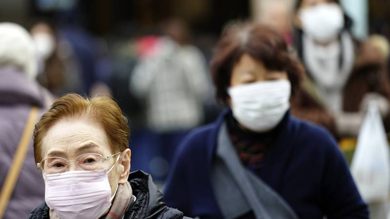 Pedestrians wear protective masks as they walk through a shopping district in Tokyo Thursday,...