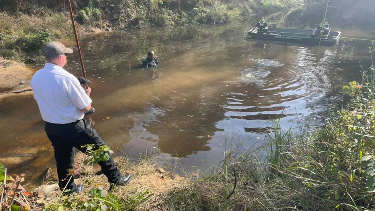 Members of the Minden Fire Department dive team search Mile Creek off Bayou Drive for a murder...