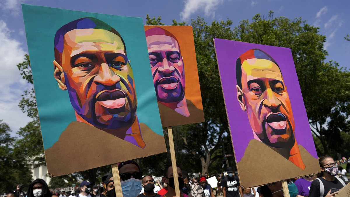 FILE - In this Aug. 28, 2020, file photo, people carry posters with George Floyd on them as...