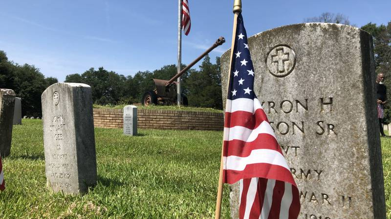 A flag stands in front of the headstone of a servicemember, as the sacrifices of those in...