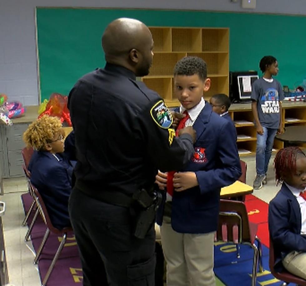 Cpl. Rodney Bradley helps a Claiborne student tie his tie.