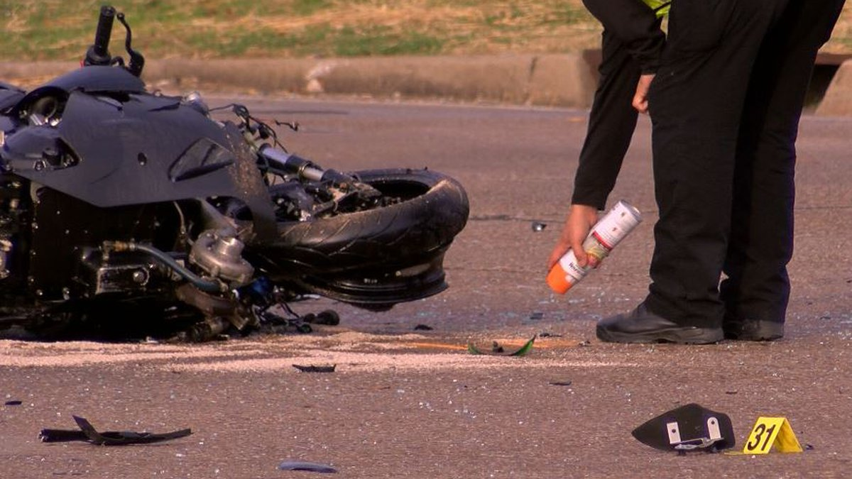 A crash investigator marks the scene of a collision that claimed a motorcyclist's life at...