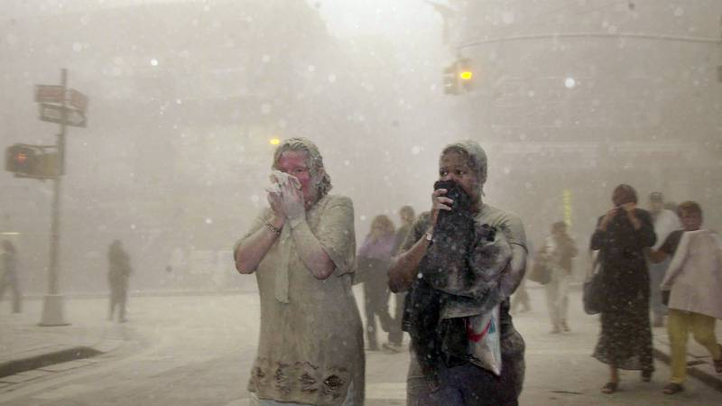 FILE — In this Sept. 11, 2001 file photo, people covered in dust from the collapsed World Trade...