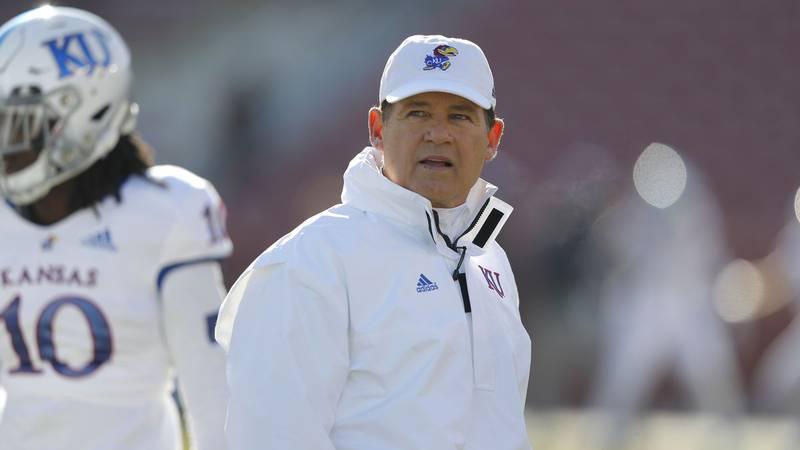 Kansas head coach Les Miles watches warm ups before an NCAA college football game against Iowa...
