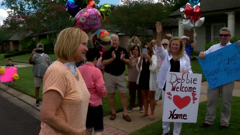 Debbie Tullos is welcomed home from the hospital by family.