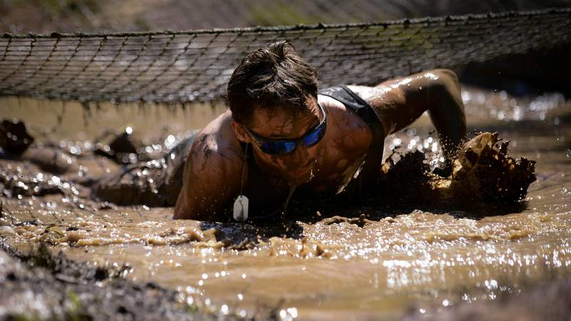 A participant, crawls through a mud pit under a cargo net during the 2017 Defenders of Liberty...