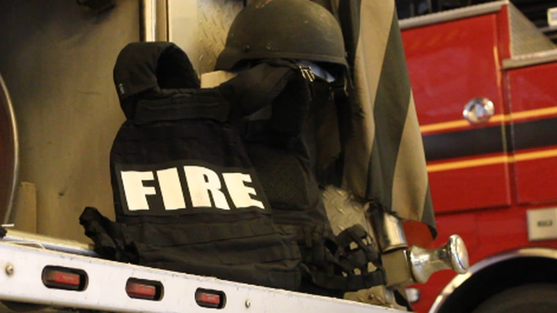 A Shreveport FIre Department ballistic vest and helmet sits on the rear of a firetruck.