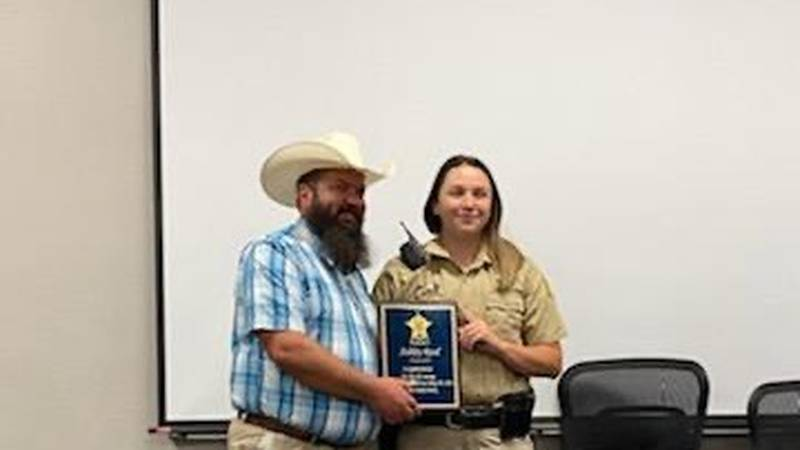 Henderson County Sheriff's Deputy Ashley Reed (right) is presented with a plaque by Sheriff...