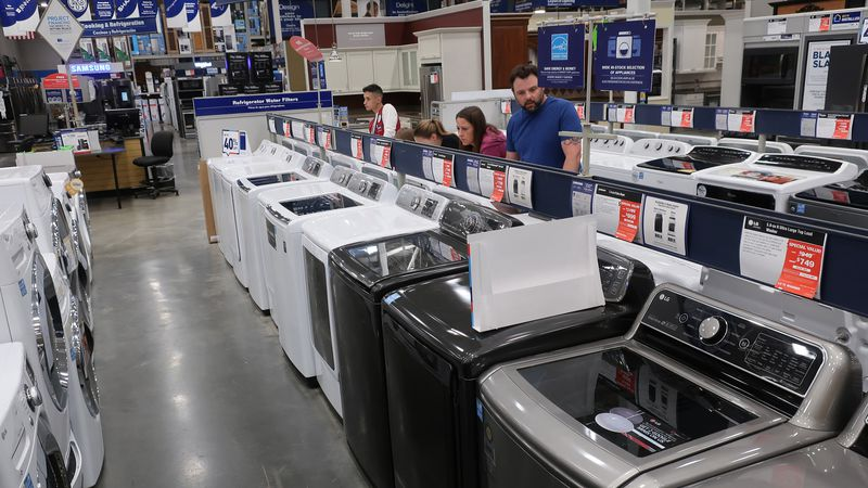 FILE- In this May 21, 2018, file photo, a family shops for washing and drying machines at...